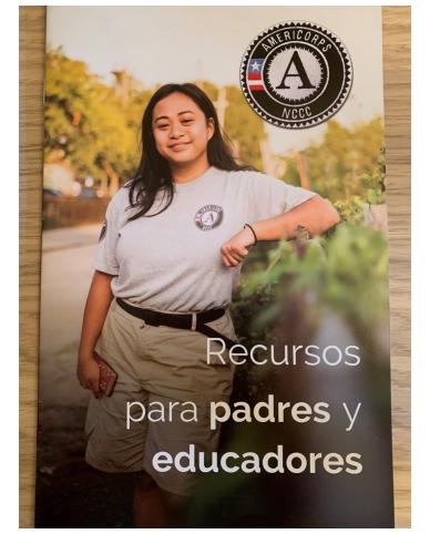"""First page of booklet contains photo of member leaning again truck bed with plants, AmeriCorps NCCC logo, and text """"Recursos para padres y educadores"""""""